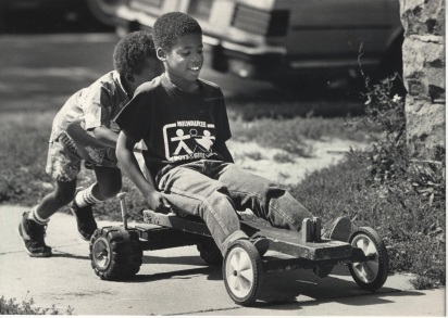 Steven Garfield, 9, got a push from Matthew Simmons, 4, while riding a homemade cart on W. Locust St. near 5th St.Thursday, August 28, 1986.